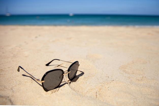 Lunettes de soleil avec sur le sable sur une plage d'été ensoleillée. le concept de voyage et de loisirs.