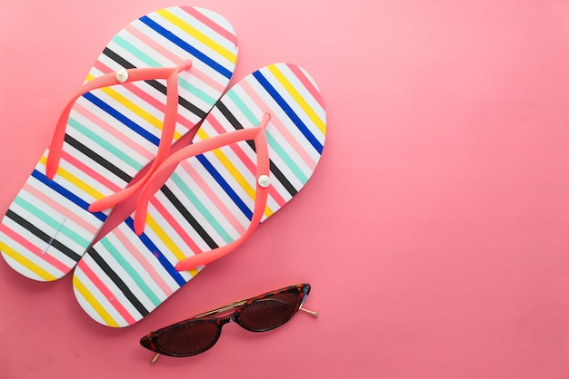 Lunettes de soleil et sandales sur fond rose de haut en bas