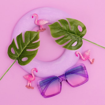 Lunettes de soleil violettes en composition tropicale. art plat à la mode minimaliste