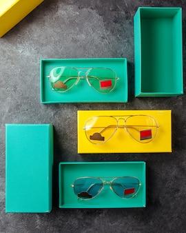 Lunettes de soleil une vue de dessus de nouvelles lunettes de soleil à l'intérieur des emballages sur la surface grise