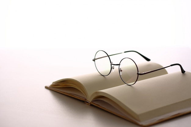 Des lunettes sont placées sur le livre. avoir un espace latéral écrit.
