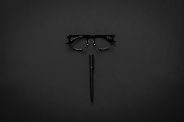 Lunettes et stylo dans un style de vie moderne sur fond sombre pour un concept minimaliste plat noir.