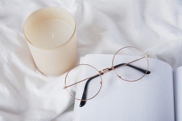 Lunettes de vue, bougie aromatique et bloc-notes vierge ouvert sur un espace de copie en tissu froissé blanc