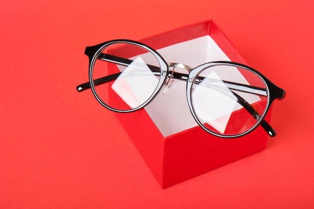 Lunettes de vue dans une boîte cadeau rouge sur l'espace de copie de fond rouge