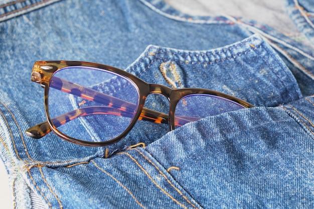 Lunettes de vue dans la poche d'une veste en jean bleue, espace de copie de lunettes tendance