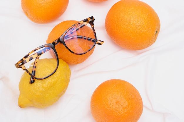 Lunettes de vue élégantes sur les oranges et le citron, les agrumes sur l'espace de copie en tissu à la menthe blanche
