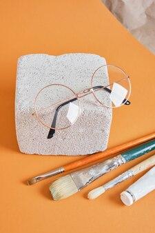Lunettes de vue sur fond marron bloc de béton, concept d'atelier d'artiste tube de peinture et pinceaux