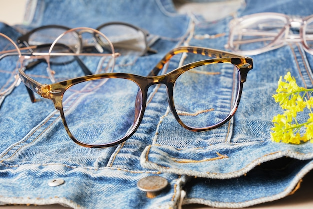 Lunettes de vue à la mode sur une veste en jean, une vieille veste en jean bleu et plusieurs lunettes, montures de lunettes à la mode