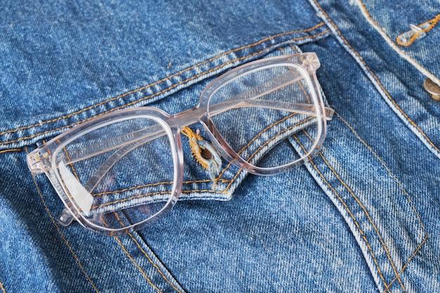 Lunettes de vue avec montures transparentes sur la poche d'une veste en jean bleu, lunettes tendance, espace de copie de style rétro