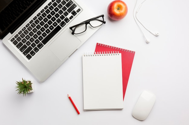 Lunettes de vue sur ordinateur portable, pomme, écouteurs, crayon de couleur, bloc-notes à spirale et souris sur un bureau blanc