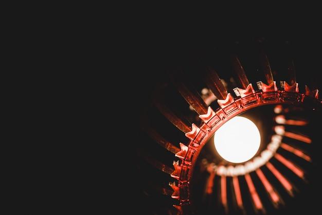 Lustre rougeoyant avec ornement rouge dans une pièce sombre sur fond noir