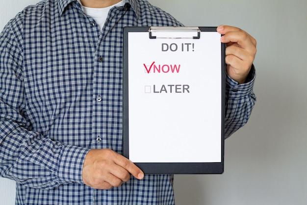 Lutte contre la procrastination et le concept d'entreprise. homme tenant une affiche en papier avec le texte «maintenant ou plus tard»
