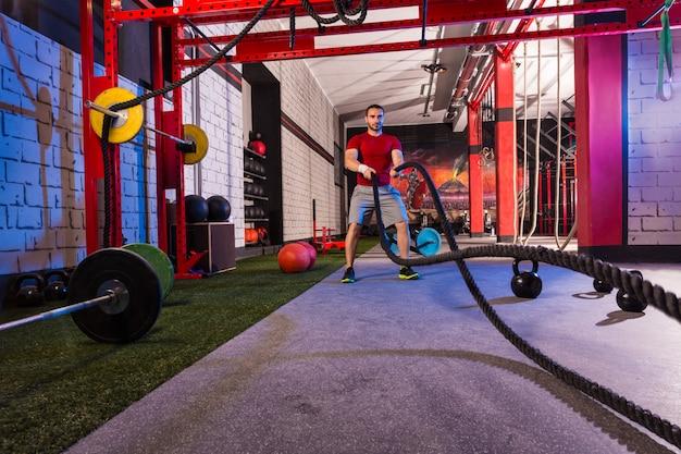 Lutter contre les cordes homme à l'exercice d'entraînement de gym