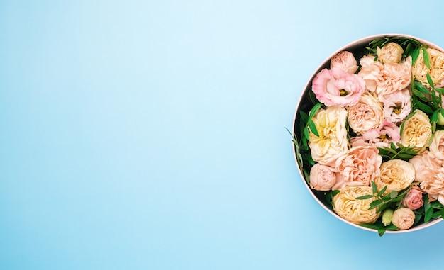Luxe belles fleurs dans une boîte ronde de chapeau sur le fond bleu avec espace de copie. cadeau ou cadeau