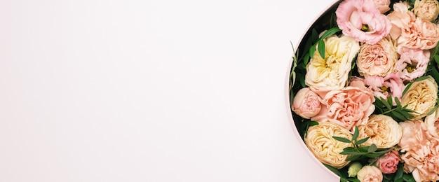 Luxe belles fleurs dans une boîte ronde de chapeau sur le fond rose avec espace de copie. cadeau ou cadeau le jour de la saint-valentin, 8 mars, fête des mères, mariage.