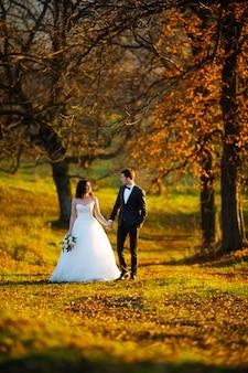 Luxe élégant jeune mariée et le marié sur le fond de la forêt verte ensoleillée de printemps