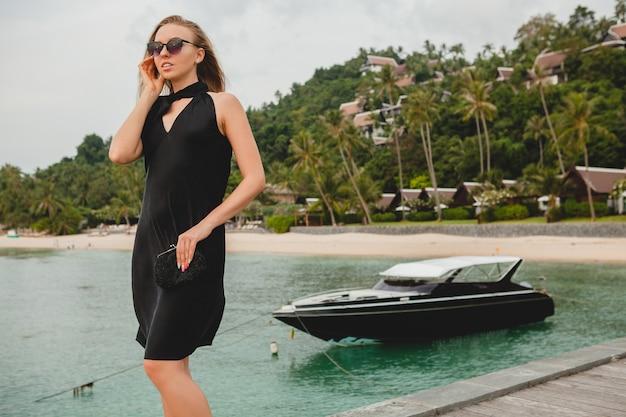Luxe sexy jolie femme vêtue d'une robe noire posant sur la jetée dans un hôtel de luxe, lunettes de soleil, vacances d'été, plage tropicale