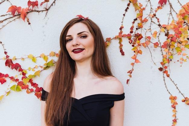 Luxueuse belle femme souriante en robe noire posant contre le mur, profitant d'une vie riche
