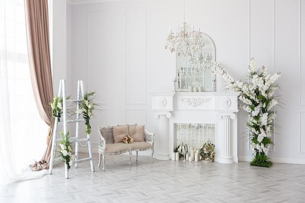 Luxueuse chambre d'hôtes spacieuse et lumineuse avec de beaux meubles chics, une immense baie vitrée dans un style royal est décorée de plantes vertes, des murs blancs avec du stuc et une cheminée
