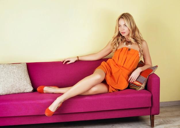 Luxueuse femme blonde dans une robe orange sur canapé violet