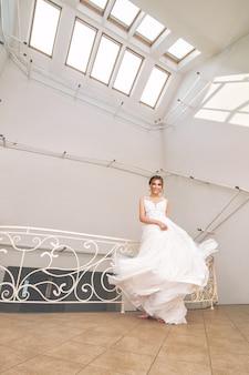 Luxueuse jeune belle mariée heureuse dans une robe de mariée à la mode dans une grande salle blanche