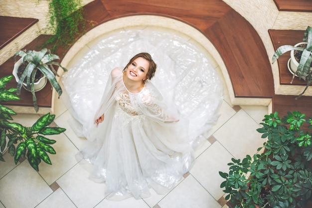 Luxueuse jeune belle mariée heureuse dans une robe de mariée à la mode dans le hall