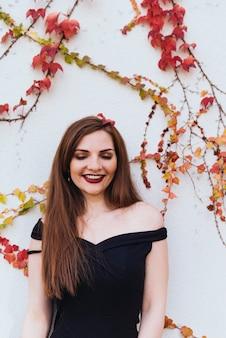 Luxueuse jeune femme aux cheveux longs en robe noire posant contre le mur à l'extérieur et souriant