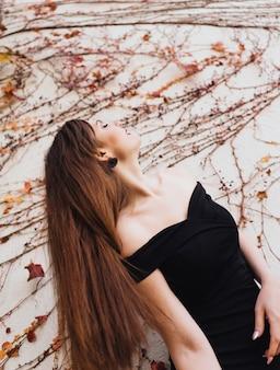 Une luxueuse jeune femme aux cheveux longs vêtue d'une robe noire posant contre un mur avec des plantes dans son jardin