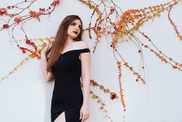 Une luxueuse jeune femme séduisante vêtue d'une robe noire se tient près du mur et profite du reste