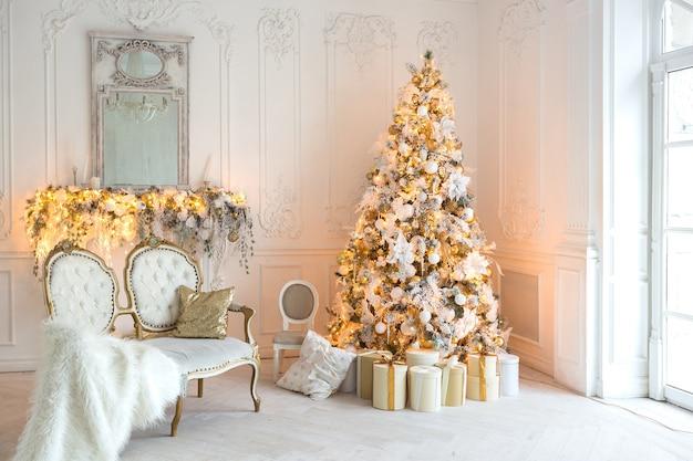 Luxueux salon intérieur lumineux et coûteux dans un style royal décoré d'un arbre de noël et de grandes fenêtres