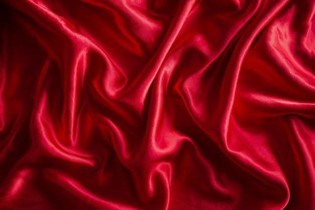 Luxueux tissu ou soie rouge satiné. abstrait de tissu de vagues douces.