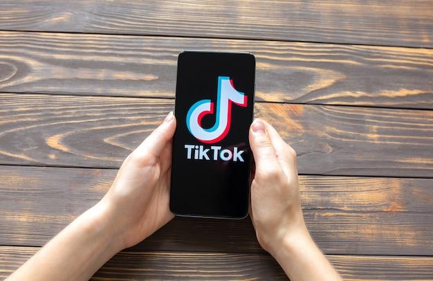 Lviv, ukraine - 25 octobre 2020 : application tik tok sur smartphone moderne. réseaux sociaux. fond en bois.