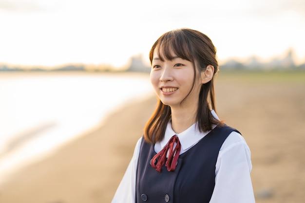Lycéen femelle asiatique marchant sur la plage