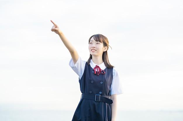 Lycéen féminin asiatique pointant vers le ciel