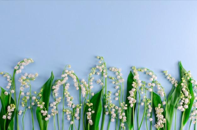 Lys de la vallée sur bleu pastel. espace de copie. concept de fleurs de printemps
