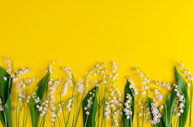 Lys de la vallée sur jaune. espace de copie. concept de fleurs de printemps
