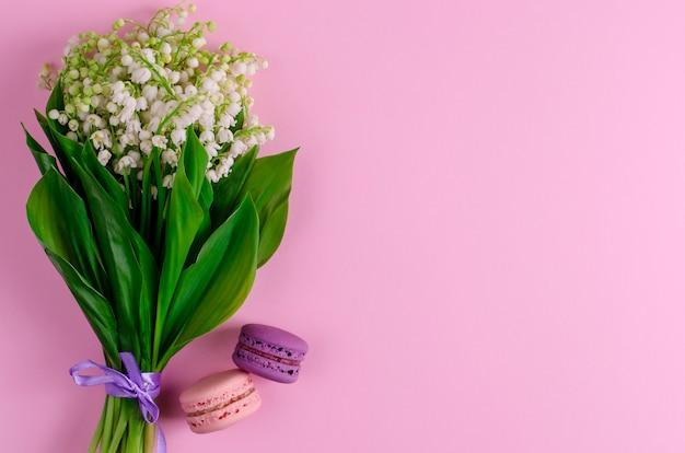 Lys de la vallée noués avec un ruban violet et des macarons sur un bleu pastel.