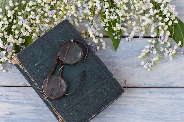 Lys de la vallée et oublie moi nots, vieux livre et lunettes