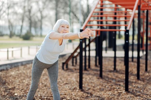 Ma belle journée. ravie de femme âgée portant des vêtements de sport et exerçant en plein air