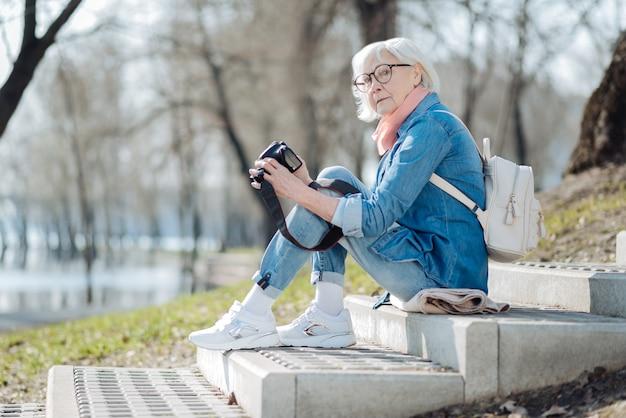 Ma caméra. ravi femme mûre assise sur les marches et regardant à travers des photos