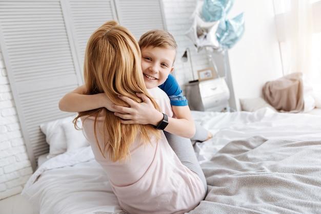 Ma chère mère. garçon agréable joyeux positif souriant et étreignant sa mère tout en lui exprimant ses sentiments
