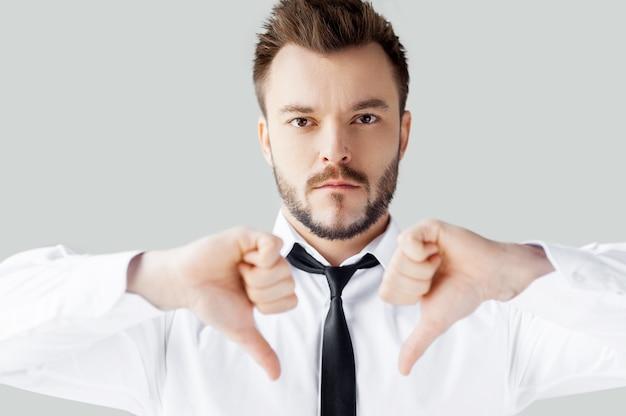 Ma décision. portrait d'un jeune homme confiant en chemise et cravate regardant la caméra et montrant ses pouces vers le bas en se tenant debout sur fond gris