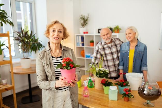 Ma fleur préférée. agréable femme âgée vous souriant tout en vous montrant un pot de fleurs