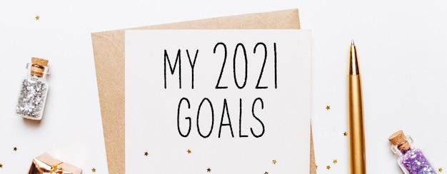 Ma note d'objectifs 2021 avec enveloppe, cadeaux et étoiles scintillantes d'or sur une surface blanche. joyeux noël et nouvel an concept