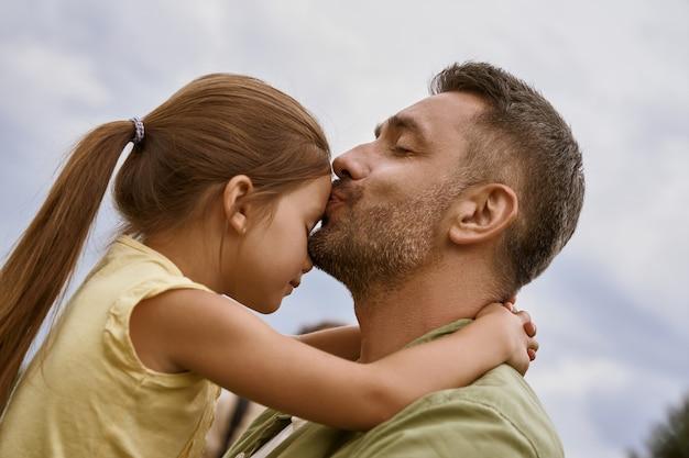 Ma petite fille jeune père aimant embrasser sa jolie fille au front tout en passant du temps