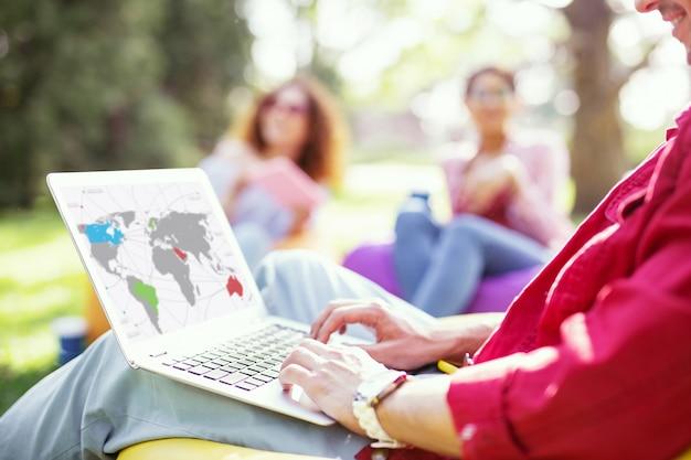 Ma startup. homme d'affaires prospère professionnel travaillant sur son projet et filles assises en arrière-plan