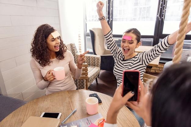 Ma victoire. énergique joyeux trois amis s'amusant tout en dégustant du thé et en participant au jeu