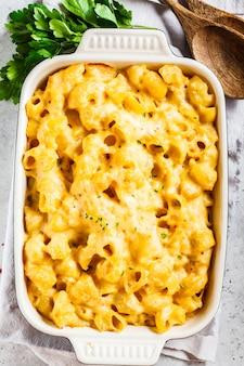 Mac et fromage dans le plat du four, fond blanc