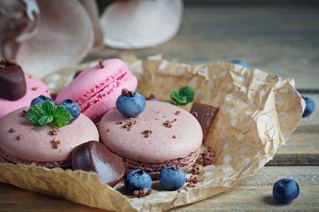 Macaron aux myrtilles fraîches et chocolat sur table en bois rustique