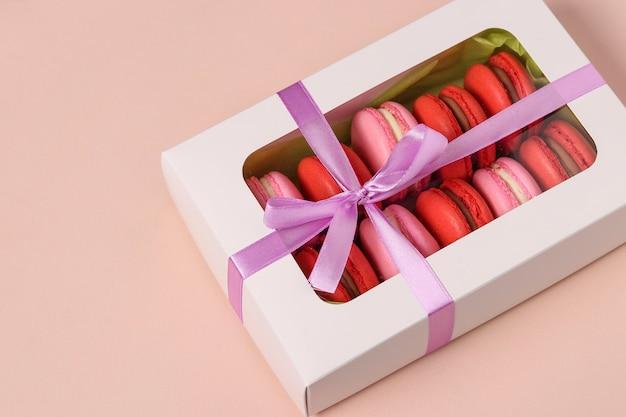 Macaron de biscuits sucrés savoureux, macaron rouge et rose dans une boîte cadeau blanche sur fond rose, orientation horizontale, gros plan